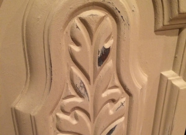 Using sandpaper to distress painted furniture.