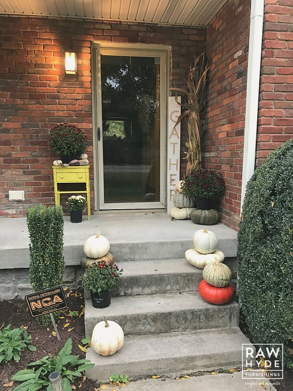 Image of my fall porch decor, including the mum pots I painted to save money on new pots!